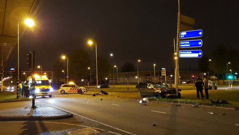 Auto in Amsterdam flink beschadigd bij botsing met stoplicht.