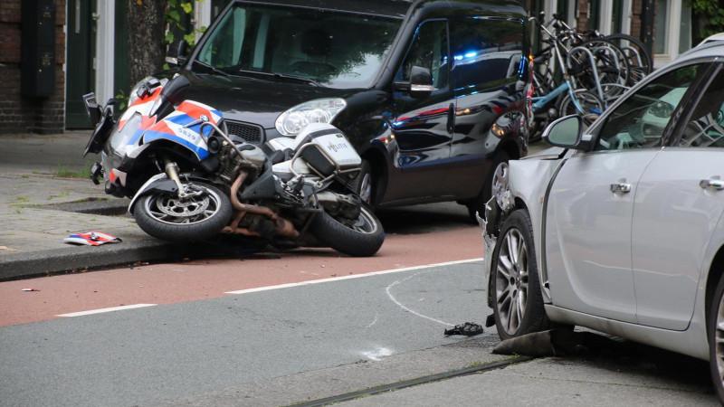 Agent en taxichauffeur naar ziekenhuis na botsing in Amsterdam.