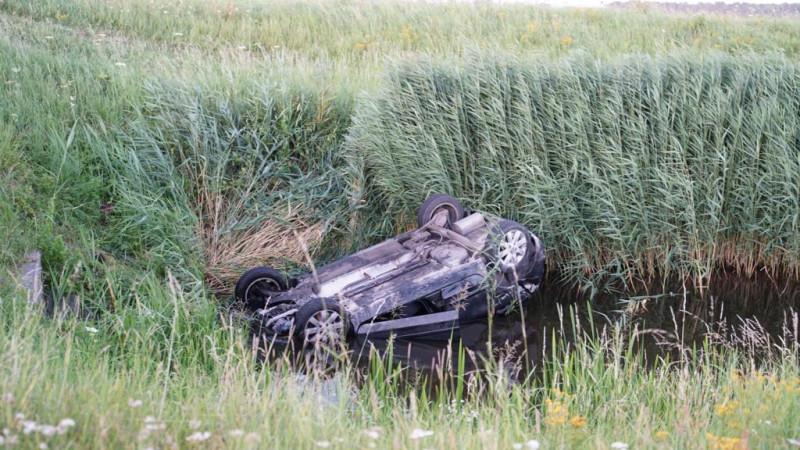 Auto in water beland bij aanrijding, bestuurder klimt zelf op de kant.