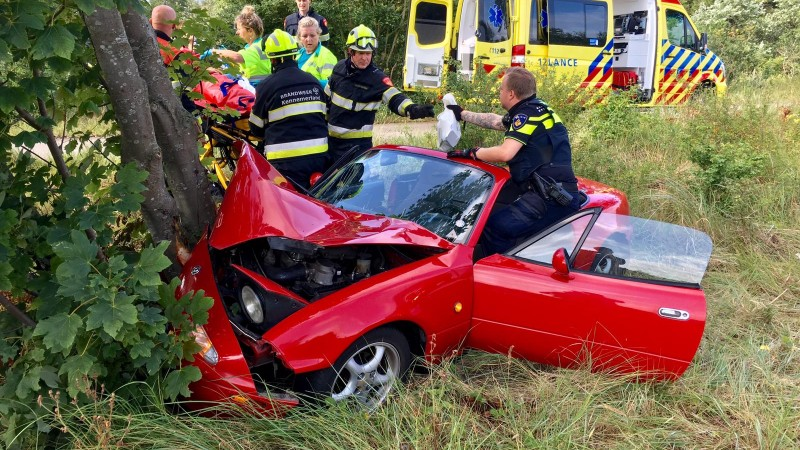 Twee mensen gewond bij heftig ongeluk met rode cabrio.