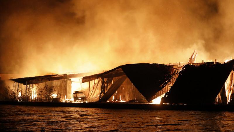 Grote uitslaande brand in loods in Halfweg