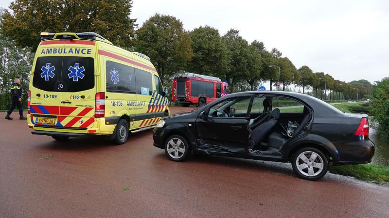 Brandweer bevrijdt automobilist uit wrak na botsing in Zwaagdijk-Oost.