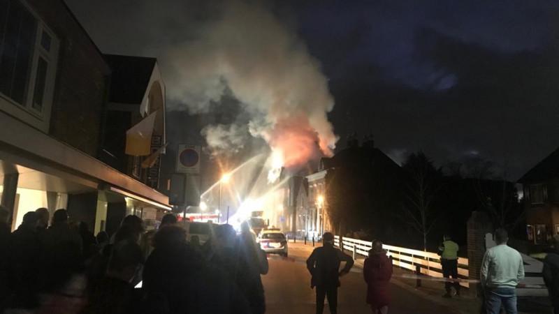 Veel mensen staan te kijken naar de brand